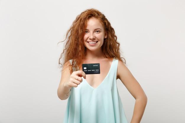 Młoda uśmiechnięta ruda kobieta dziewczyna w dorywczo lekkie ubrania pozowanie na białym tle na białym tle, portret studio. koncepcja życia szczere emocje ludzi. makieta miejsca na kopię. posiadanie karty kredytowej banku.