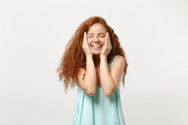 Młoda uśmiechnięta ruda kobieta w dorywczo lekkie ubrania pozowanie na białym tle. koncepcja życia szczere emocje ludzi. makieta miejsca na kopię. trzymając oczy zamknięte, kładąc ręce na policzkach.