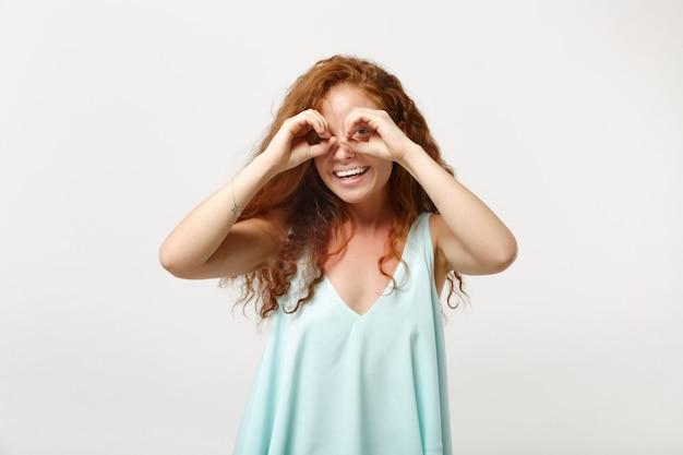 Młoda uśmiechnięta ruda kobieta w dorywczo lekkie ubrania pozowanie na białym tle na tle białej ściany. koncepcja życia ludzi. makieta miejsca na kopię. trzymanie rąk w pobliżu oczu, imitujące okulary lub lornetkę.