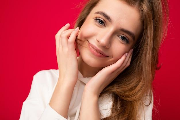 Młoda uśmiechnięta seksowna piękna ciemna blondynka ze szczerymi emocjami na białym tle