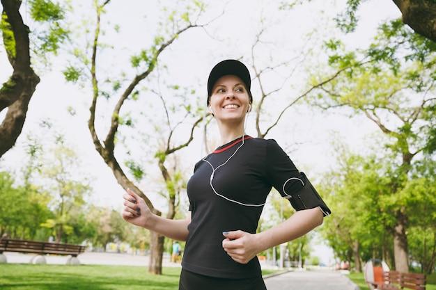 Młoda uśmiechnięta sportowa brunetka kobieta w czarnym mundurze i czapce ze słuchawkami trenuje uprawianie sportu, bieganie i słuchanie muzyki na ścieżce w parku miejskim na zewnątrz