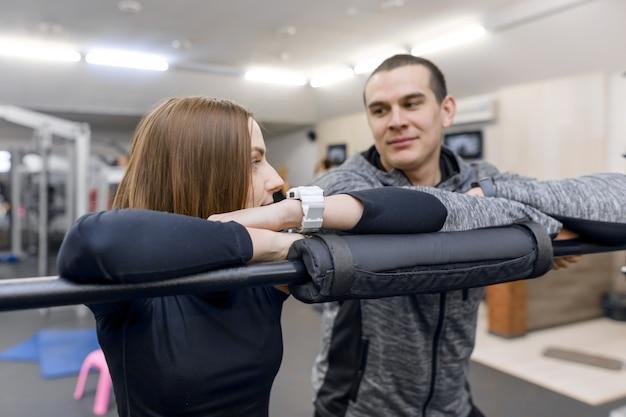 Młoda uśmiechnięta sprawności fizycznej para opowiada w gym