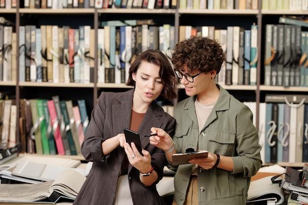 Młoda uśmiechnięta sprzedawczyni lub konsultantka studia projektowego, wskazując na ekran smartfona trzymanego przez klientkę, przewijająca próbki