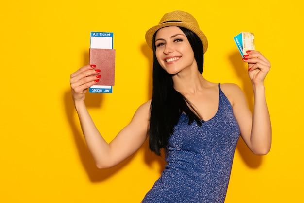 Młoda uśmiechnięta studentka podekscytowana trzyma paszport karta pokładowa bilet i karta kredytowa
