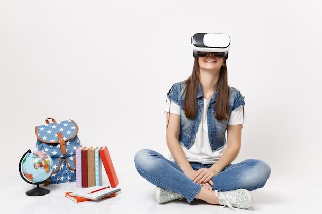 Młoda uśmiechnięta studentka w okularach wirtualnej rzeczywistości, patrząc na bok, ciesząc się siedzeniem w pobliżu kuli ziemskiej, plecaka, podręczników szkolnych na białym tle