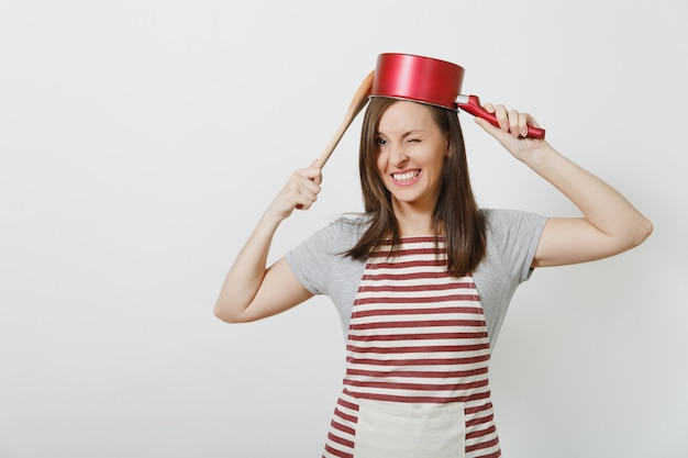 Młoda uśmiechnięta szalona gospodyni domowa w pasiasty fartuch, szary t-shirt na białym tle. piękna, zabawna kobieta gospodyni trzymająca czerwoną pustą patelnię na głowie drewnianą łyżką