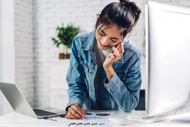Młoda uśmiechnięta szczęśliwa azjatykcia kobieta relaksuje używać laptopu działanie i wideokonferencja spotyka czat online młoda kreatywnie dziewczyny spojrzenie na biznesowego raportu papier w domu. praca od domu pojęcia