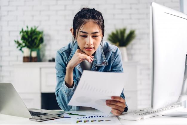 Młoda uśmiechnięta szczęśliwa azjatykcia kobieta relaksuje używać laptopu działanie i wideokonferencja spotyka online gadkę. młody kreatywnie dziewczyny spojrzenie na biznesowego raportu papier w domu. praca z domu koncepcji