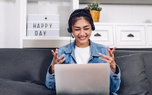 Młoda uśmiechnięta szczęśliwa piękna azjatykcia kobieta relaksuje używać laptopu działanie i wideokonferencja spotyka w domu. młoda kreatywna dziewczyna rozmawiać z zestawu słuchawkowego. praca z domu koncepcji