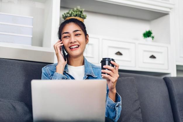 Młoda uśmiechnięta szczęśliwa piękna azjatykcia kobieta relaksuje używać laptopu działanie i wideokonferencja spotyka w domu młoda kreatywnie dziewczyny rozmowa z smartphone i pije kawę. praca z domu koncepcji