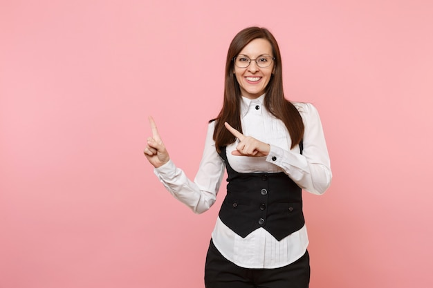 Młoda uśmiechnięta udanego biznesu kobieta w garniturze i okularach, wskazując palcem wskazującym na bok na białym tle na pastelowym różowym tle. szefowa. koncepcja bogactwa kariery osiągnięcia. skopiuj miejsce na reklamę.
