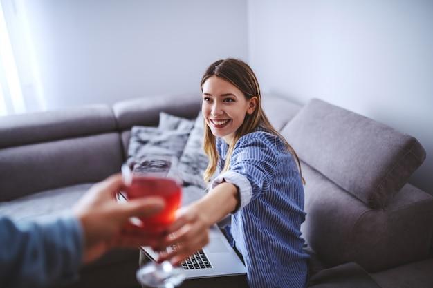 Młoda uśmiechnięta urocza caucasian brunetka w pasiastej koszuli siedzi na kanapie w salonie i dostaje kieliszek wina od swojego chłopaka.