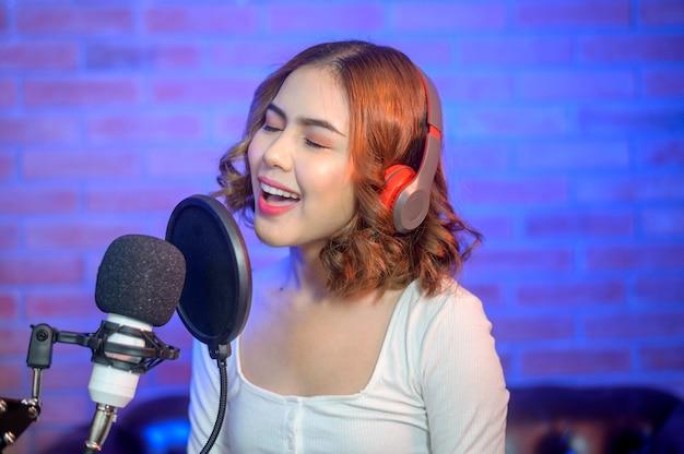 Młoda uśmiechnięta wokalistka w słuchawkach z mikrofonem podczas nagrywania piosenki w studiu muzycznym z kolorowymi światłami.