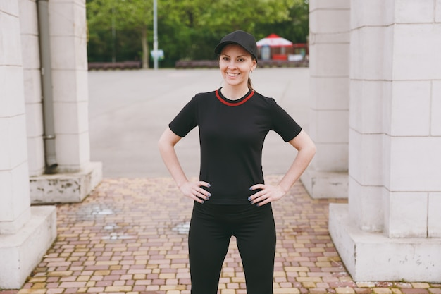 Młoda uśmiechnięta wysportowana piękna brunetka w czarnym mundurze i czapce, wykonująca ćwiczenia sportowe, rozgrzewka przed bieganiem, stojąca w parku miejskim na zewnątrz