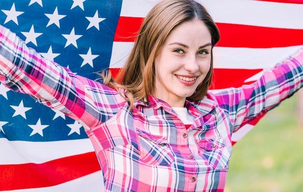 Młoda uśmiechnięta żeńska falowanie flaga amerykańska na dniu niepodległości