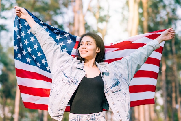 Młoda uśmiechnięta żeńska trzyma flaga usa na czwartego lipca
