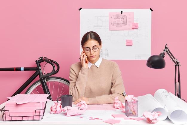 Młoda utalentowana architektka robi szkice planowania budynku, rozmawia przez telefon w proces pracy, otoczona papierowymi planami pozuje na pulpicie