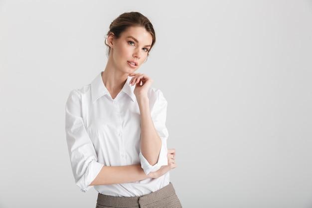 Młoda uwodzicielska kobieta pozuje i wygląda bezpośrednio odizolowana na białym tle