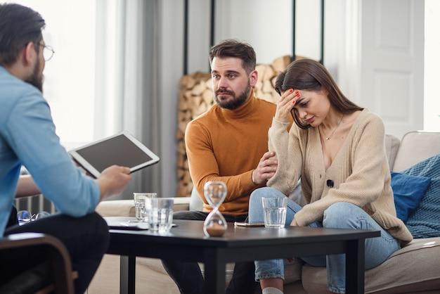 Młoda walcząca z gniewną parą obwiniająca się nawzajem za problemy, opowiadająca się za twoją winę, dyskutująca z psychologiem, kto jest dobry i zły, nieporozumienia i samolubstwo w małżeństwie.