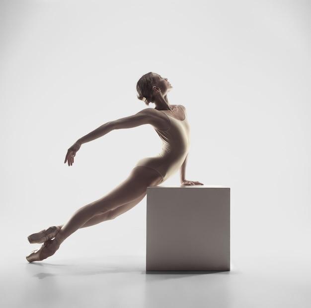 Młoda wdzięczna tancerka baletowa lub klasyczna baletnica tańcząca na białym studiu