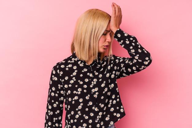 Młoda wenezuelka na różowej ścianie zapomina o czymś, klepie dłonią w czoło i zamyka oczy.