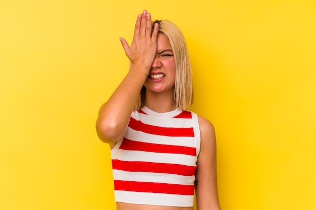 Młoda wenezuelka na żółtej ścianie zapomina o czymś, klepie dłonią w czoło i zamyka oczy.