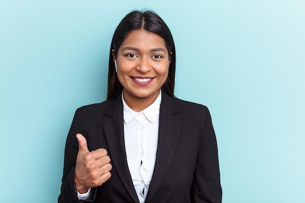 Młoda wenezuelska kobieta biznesu odizolowana na niebieskim tle uśmiecha się i podnosi kciuk w górę
