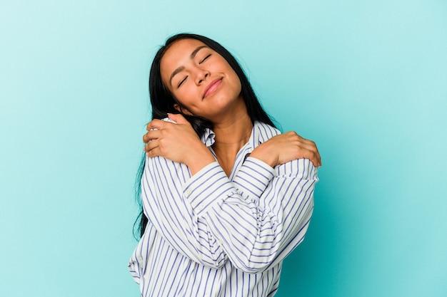 Młoda wenezuelska kobieta na białym tle na niebieskim tle przytula się, uśmiechając się beztrosko i szczęśliwie.