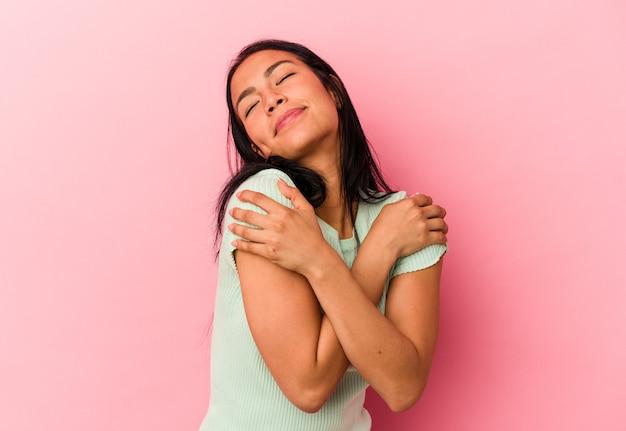 Młoda wenezuelska kobieta na białym tle na różowym tle przytula się, uśmiechając się beztrosko i szczęśliwie.