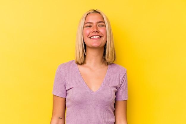 Młoda wenezuelska kobieta na żółtym tle śmieje się i zamyka oczy, czuje się zrelaksowana i szczęśliwa.