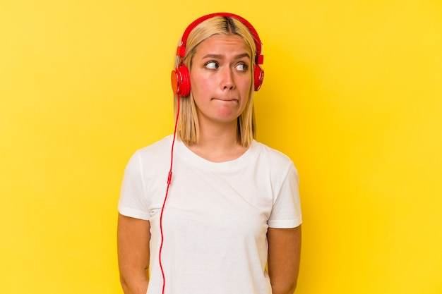 Młoda wenezuelska kobieta słuchająca muzyki na żółtym tle zdezorientowana, ma wątpliwości i niepewność.