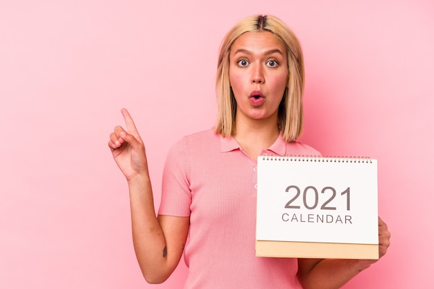 Młoda wenezuelska kobieta trzyma kalendarz na białym tle na różowym tle, wskazując na bok