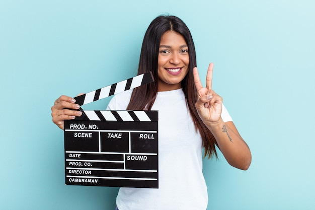 Młoda wenezuelska kobieta trzyma klaps na białym tle na niebieskim tle pokazując numer dwa palcami.