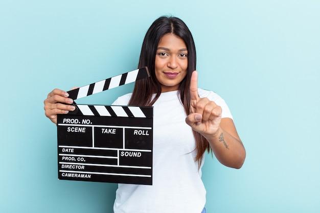 Młoda wenezuelska kobieta trzyma klaps na białym tle na niebieskim tle pokazując numer jeden palcem.