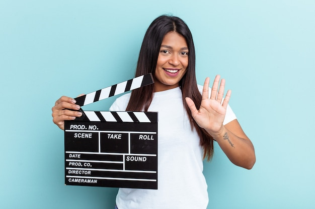 Młoda wenezuelska kobieta trzyma klaps na białym tle na niebieskim tle uśmiechając się wesoło pokazując numer pięć palcami.
