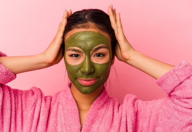 Młoda wenezuelska kobieta ubrana w szlafrok i maskę na twarz na różowym tle
