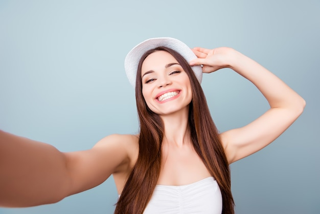 Młoda wesoła atrakcyjna brązowowłosa ząbkowata dama uśmiecha się na jasnoniebieskiej przestrzeni. robi selfie aparatem swojego telefonu, ubrana w swobodny letni strój i kapelusz