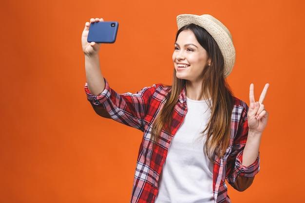 Młoda wesoła atrakcyjna brunetka uśmiecha się i bierze selfie w aparacie swojego telefonu