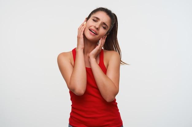 Młoda wesoła brunetka dama ubrana w czerwoną koszulkę słucha ulubionej piosenki na słuchawkach, śpiewa z zamkniętymi oczami, stoi na białym tle.