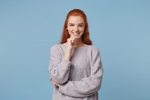 Młoda, wesoła, całkiem atrakcyjna dziewczyna o otwartym sercu z rudymi włosami stoi szeroko uśmiechnięta