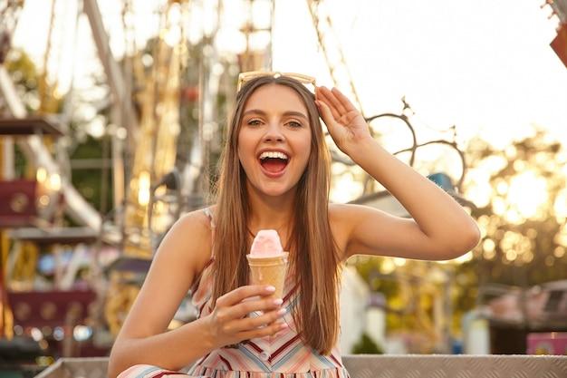 Młoda wesoła, długowłosa ładna dama z okularami przeciwsłonecznymi na głowie, patrząca z szerokim uśmiechem, jedząca lody podczas spaceru po parku atrakcji, ubrana w letnie ubrania