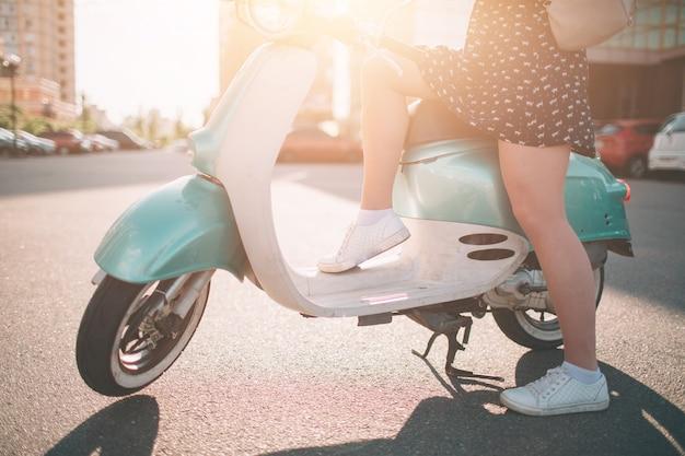 Młoda wesoła dziewczyna jazdy skuterem w mieście. portret młodej i stylowej kobiety z motorowerem