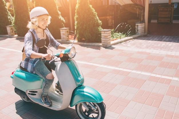 Młoda wesoła dziewczyna jazdy skuterem w mieście