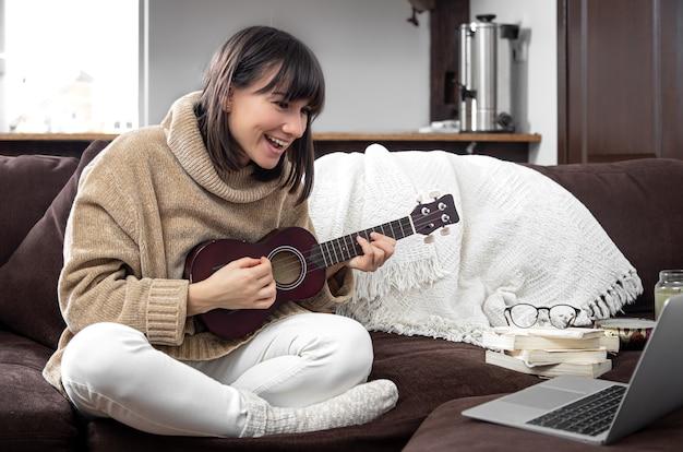 Młoda wesoła dziewczyna uczy się grać na ukulele. koncepcja edukacji online, edukacji domowej.