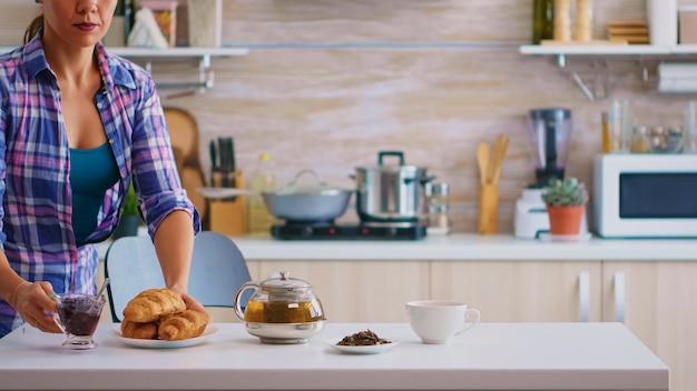 Młoda wesoła gospodyni o śniadanie picia zielonej herbaty. strzał z rozmyciem tła pani o wielki poranek z smaczne naturalne zdrowe herbaty ziołowe siedzi w kuchni.