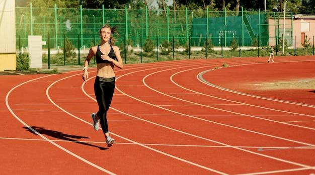 Młoda wesoła kobieta biegacz w odzieży sportowej na torze stadionu z czerwoną powłoką na zewnątrz