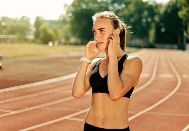 Młoda wesoła kobieta biegacz w odzieży sportowej słucha muzyki w słuchawkach na zewnątrz stadionu pokrytego czerwoną powłoką