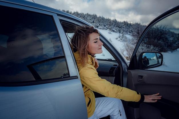 Młoda wesoła kobieta pozowanie na samochód i śnieg lasu. atrakcyjna kobieta ubrana w żółtą kurtkę siedzącą na siedzeniu pasażera w srebrnym samochodzie, sezon zimowy