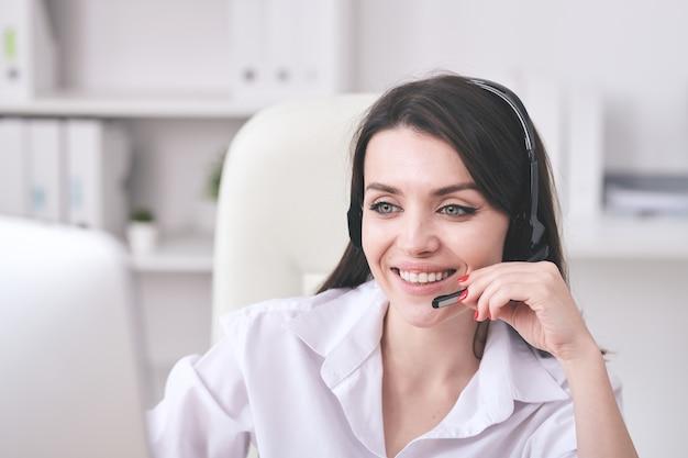 Młoda wesoła kobieta przedstawiciel obsługi klienta z zestawem słuchawkowym patrząc na ekran komputera podczas konsultacji z klientami online