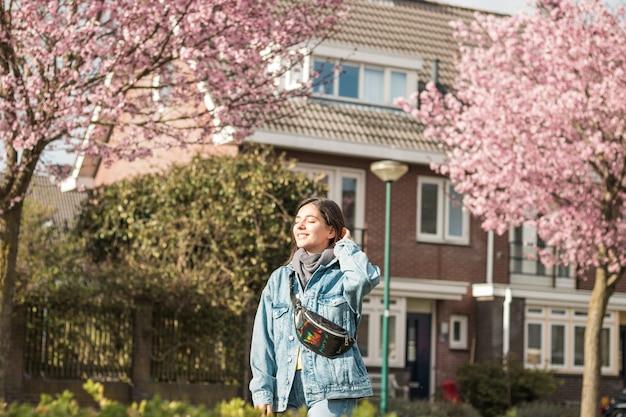 Młoda wesoła kobieta rasy mieszanej na świeżym powietrzu przed swoim domem, biorąc trochę świeżego powietrza w promieniach słońca po kwarantannie.